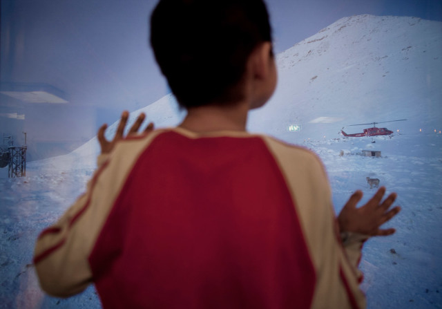 Asiaq (8) watches the helicopter landing outside the classroom window in Siorapaluk, the northernmost village in Greenland. Foto: Andrea Gjestvang